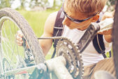 Cyclist checks chain of bicycle — Stock Photo