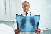 Older doctor examines x-ray image — Stock Photo