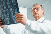 Older doctor examines MRI image — Stock Photo