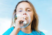 Girl blowing soap bubble — Stock Photo
