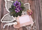 Photo frame, knitted napkins and viola — Stock Photo