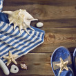 Beach flip flops, striped dress, seashells on a wooden floor. — Stock Photo