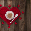 Cup of coffee with whipped cream on a red knitted heart. — Stock Photo