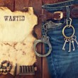 Background in the style of the American West. Handcuffs in jeans — Stock Photo