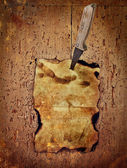 Paper pinned with a knife to the old wooden wall — Stock Photo