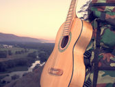 Landscape with a backpack and a guitar — Stock Photo