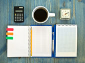 Office supplies and checked notebook on wood background — Stock Photo