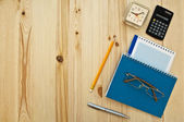 Office supplies and glasses on wood background — Stock Photo