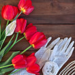 Red tulips and white lace gloves on wooden background — Stock Photo #45428431