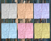 Colorful sheets of crumpled paper on wooden texture dark — Stock Photo