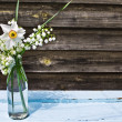 Bouquet of white spring flowers in a bottle on blue wooden table — Stock Photo