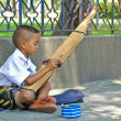 Stock Photo: Poor School Boy Perform Traditional Music for Money