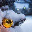 Bright Gold Ornament Hangs From Snow Covered Christmas Tree — Stock Photo #30765433