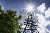 Linee ad alta tensione e luminoso sole illustrano estate esigenze di potenza — Foto Stock