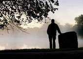 Silhouetted Adult Male Stands Alone Thoughtfully Staring Towards Foggy Lake — Stock Photo