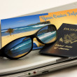 Sunglasses reflect an exotic Caribbean beachwith international passport, cruise information and travel laptop — ストック写真