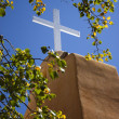 Cross glows brightly atop a mission building  — Stock Photo