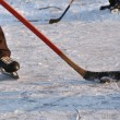 Stock Photo: Hockey stick and ice skate in fragment of leisure hockey game