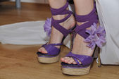 Legs in violet heels with flower — Stock Photo