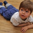 Curious small boy lying on wooden floor — Stock Photo