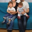 Happy family sitting on blue sofa — Stock Photo