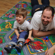 Son and father playing with toys on carpet — Stock Photo