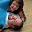 Happy couple wrapped in blue blanket — Stock Photo