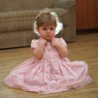Stock Photo: Frown sitting girl in pink dress wit backlighted hairs