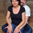 Stock Photo: Happy couple sitting on wooden floor