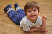 Happy small boy lying on wooden floor — Stockfoto