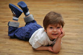 Happy relaxing small boy lying on wooden floor — Stock Photo