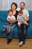 Счастливая семья, сидя на синий диван — Стоковое фото
