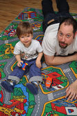Son and father playing with toys on carpet — Photo