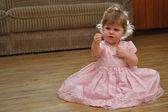Small girl in pink dress couriosly looking at her hand — Photo