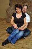 Happy couple sitting on wooden floor — Stock Photo