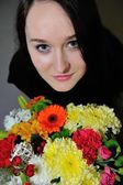 Beautiful young woman with bunch of flowers  — Stock Photo