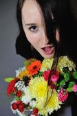 Beautiful young woman with bunch of flowers  — Stockfoto