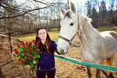 Mooie jonge vrouw met bos van rozen en wit paard — Stockfoto