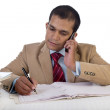 Young Business Executive at Work and talking on phone while at his desk amidst a pile of files. — Stock Photo