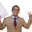 A happy and elated businessman holding a paper and showing Victory sign. — Stock Photo