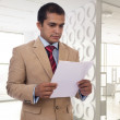 Young Businessman reading a piece of paper — Stock Photo