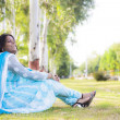 A Joyful happy asian woman sitting on the grass under a tree and laughing. — Stock Photo
