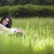 A Joyful happy woman sitting on the grass and smiling in a natural environment. — Stockfoto