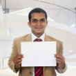 Businessman holding a blank placard. — Stock fotografie