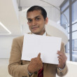 Businessman holding a blank placard and pointing with his finger. — Stock Photo