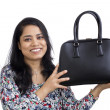 Closeup of a young Asian Indian woman showing off her handbag.  — Stockfoto