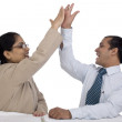 Stock Photo: Young Business Duo Celebrating and giving each other a High Five