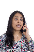 Concerned Indian woman talking on a telephone. — Stock Photo