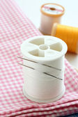Sewing thread, needles and textiles — Stock Photo