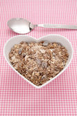 Muesli in a heart shaped bowl — Stock Photo